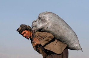 An Afghan carries a sack of coal on his back outside Kabul